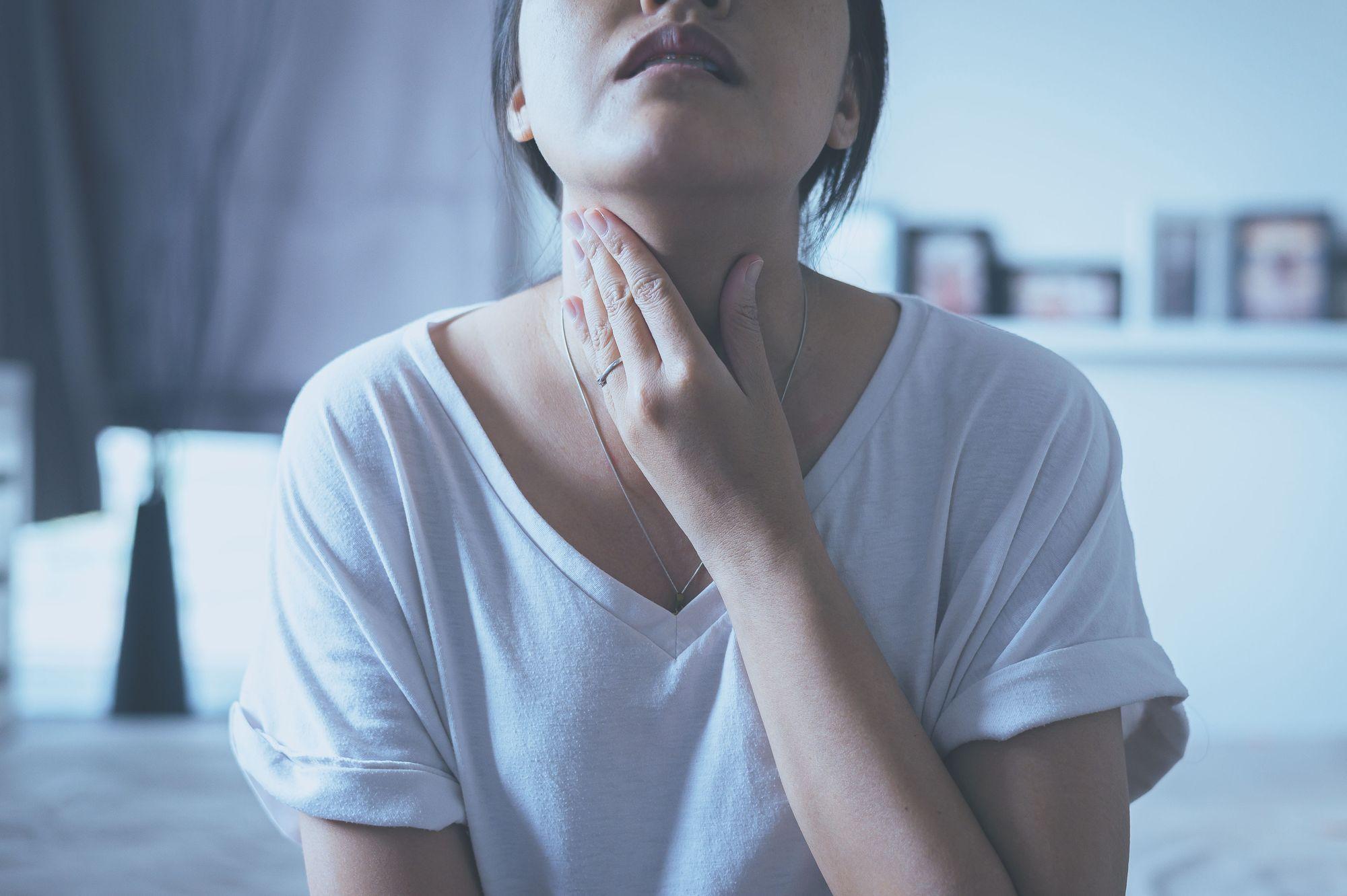 Woman holding throat
